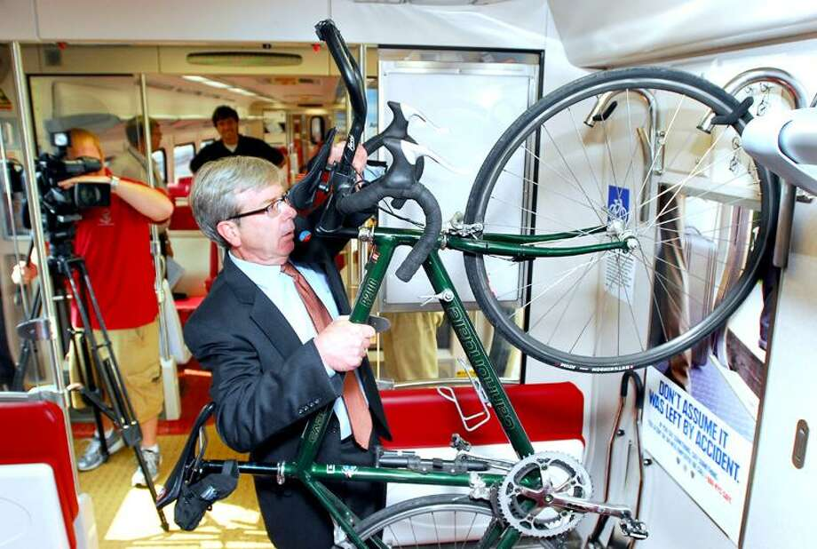 Eugene Colonese, Rail Administrator for the Ct. Dept. of Transportation, demonstrates one of two bicycle rack prototypes on an M-8 rail car at Union Station in New Haven on 9/15/2011.Photo by Arnold Gold/New Haven Register  AG0424C