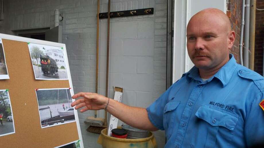 Milford Fire Capt. Chris Zak shows photos of storm-affected locations. Brian McCready/Register