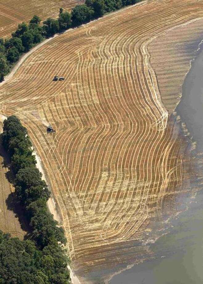 Farmers work to harvest crops as floodwaters from the Mississippi River creep across their fields in Natchez, Miss., Tuesday. Associated Press Photo: AP / AP