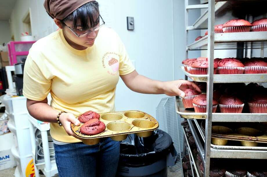 Chelsea Rivera takes red velvet cupcakes out of baking pans at Charli's Cupcake Factory in West Haven. (Arnold Gold/Register)