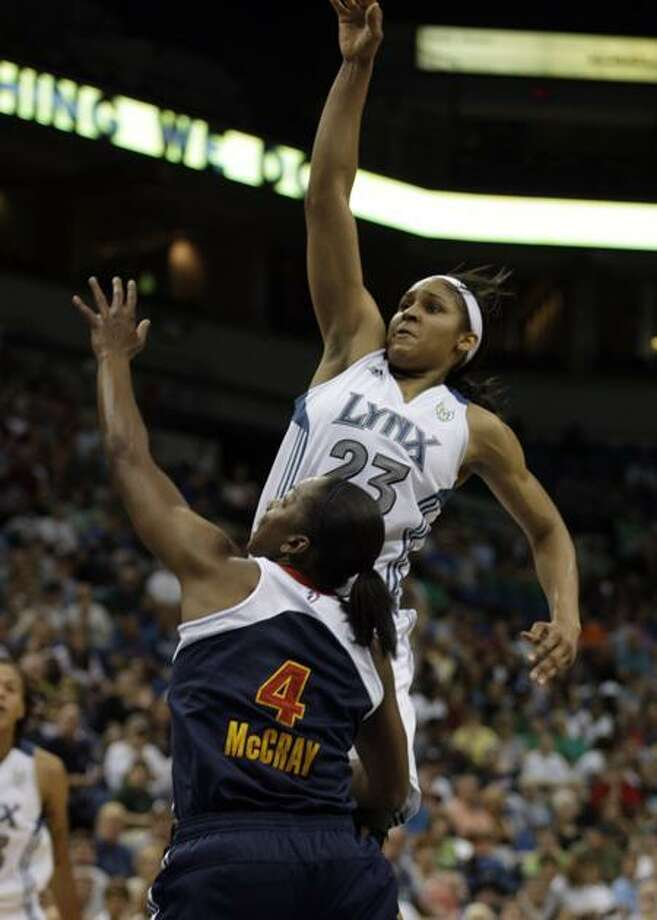 Minnesota Lynx forward Maya Moore (23) puts up a shot over Connecticut Sun guard Danielle McCray (4) during the second half of a WNBA basketball game, Saturday, July 9, 2011, in Minneapolis. Moore had a game-high 26 points as Minnesota won 90-67. (AP Photo/Paul Battaglia) Photo: AP / AP2011