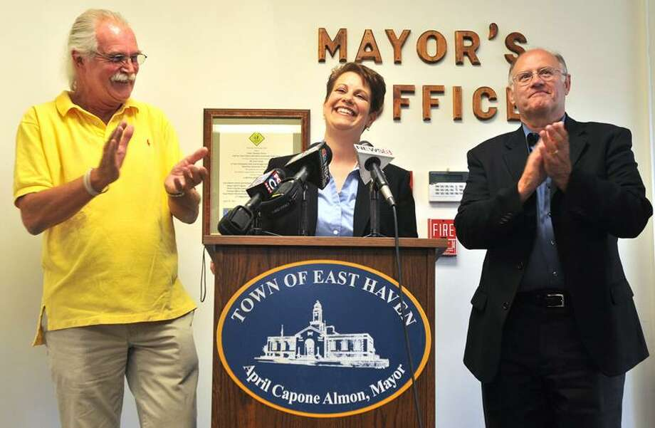 From left, Tweed-New Haven Airport Commission member Peter Leonardi, left, and Town Finance Director Tom Thompson, right, applaud East Haven Mayor April Capone Almon after she announced the sale of land to Tweed New Haven Regional Airport for $1.5 million. Brad Horrigan/Register