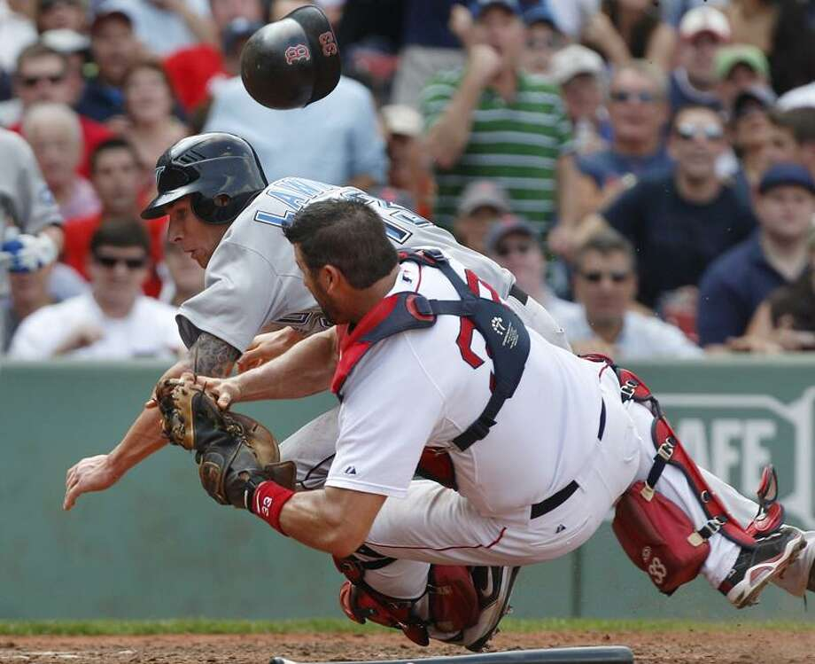 Boston Red Sox catcher Jason Varitek loses his helmet but hangs onto the ball as he collides with Toronto Blue Jays Brett Lawrie, who unsuccessfully tried to score on a fielder's choice hit by Adam Loewen, during the sixth inning of a baseball game at Fenway Park in Boston, Wednesday Sept. 14, 2011. (AP Photo/Charles Krupa) Photo: AP / AP2011