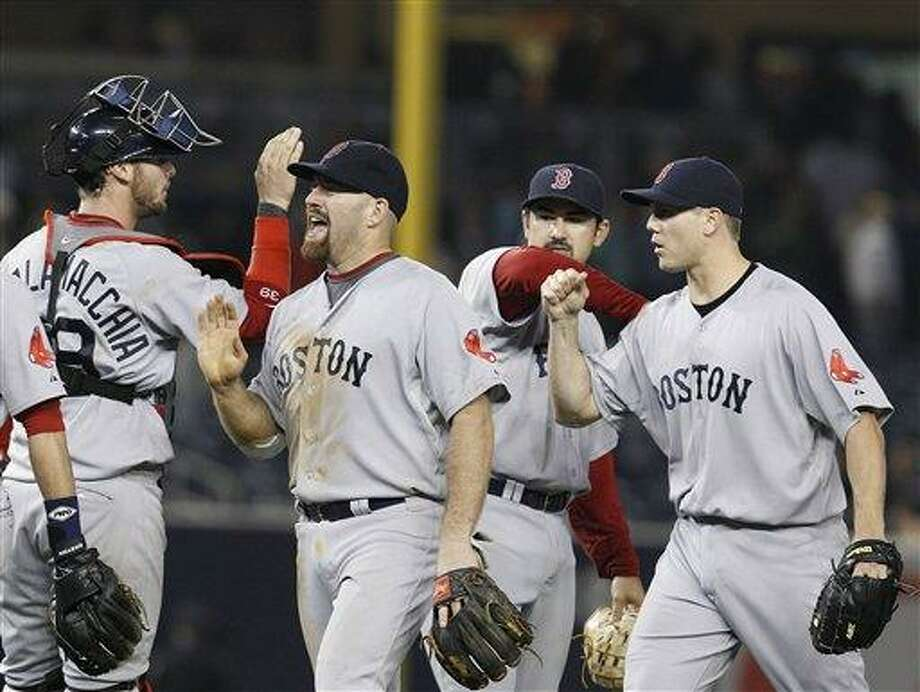Teammates, including catcher Jarrod Saltalamacchia congratulate Boston Red Sox Kevin Youkilis, second from left, after he led the Red Sox to their 7-5 victory over the New York Yankees for a three-game sweep in their baseball series at Yankee Stadium Sunday, May 15, 2011, in New York.  Red Sox closer Jonathan Papelbon, right, and first baseman Adrian Gonzalez join in the celebration. (AP Photo/Kathy Willens) Photo: ASSOCIATED PRESS / AP2011