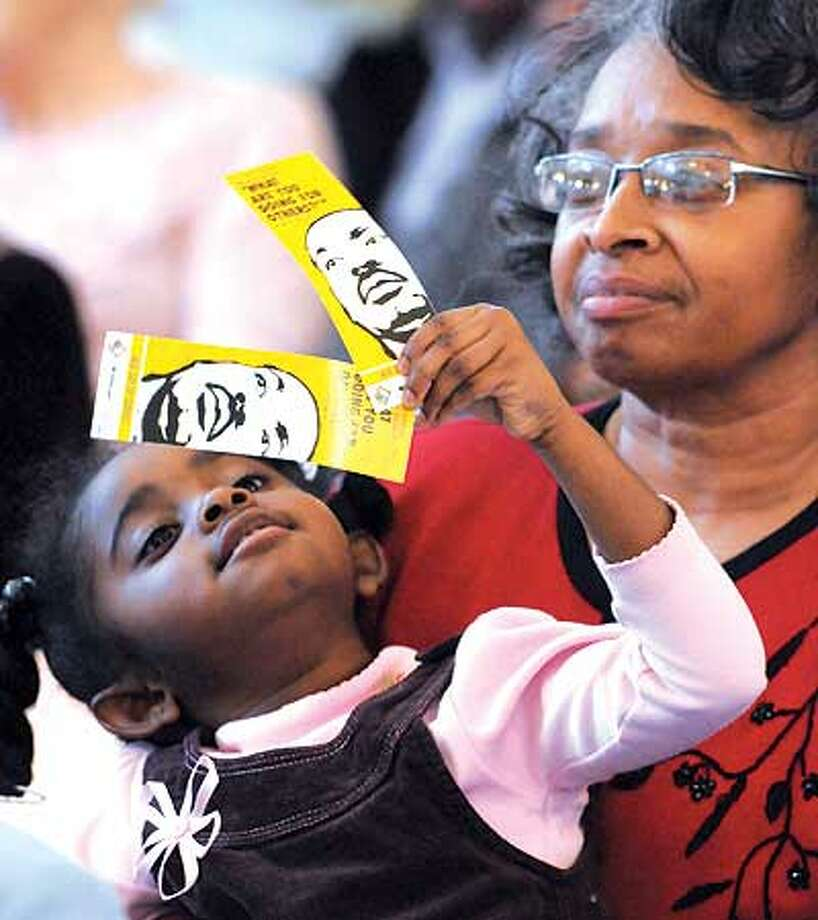 Melanie Thomas Ferguson, 4, looks at bookmarks celebrating the Rev. Martin Luther King Jr. as she sits on the lap of Vendette Thomas, her grandmother, at Reflections XXV, an event at Milford City Hall Sunday commemorating King's birthday Saturday. The two are from Stratford. See story and another photo on B1. (Mara Lavitt/Register)