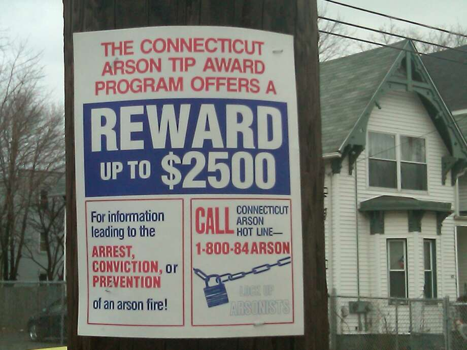 Signs such as this one offering a reward have gone up in the neighborhood where three New Haven residents died in an arson fire. Photo by William Kaempffer