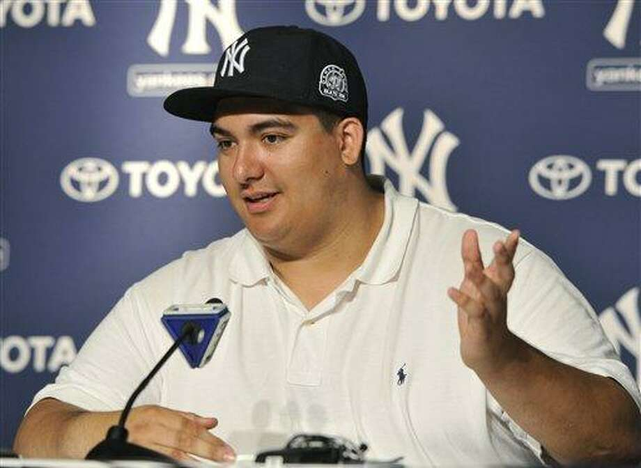 Christian Lopez speaks about catching New York Yankees' Derek Jeter's 3, 000th career hit ball at a press conference after the baseball game against the Tampa Bay Rays on Saturday, July 9, 2011 at Yankee Stadium in New York. The Yankees won 5-4. (AP Photo/Kathy Kmonicek) Photo: AP / FR170189 AP