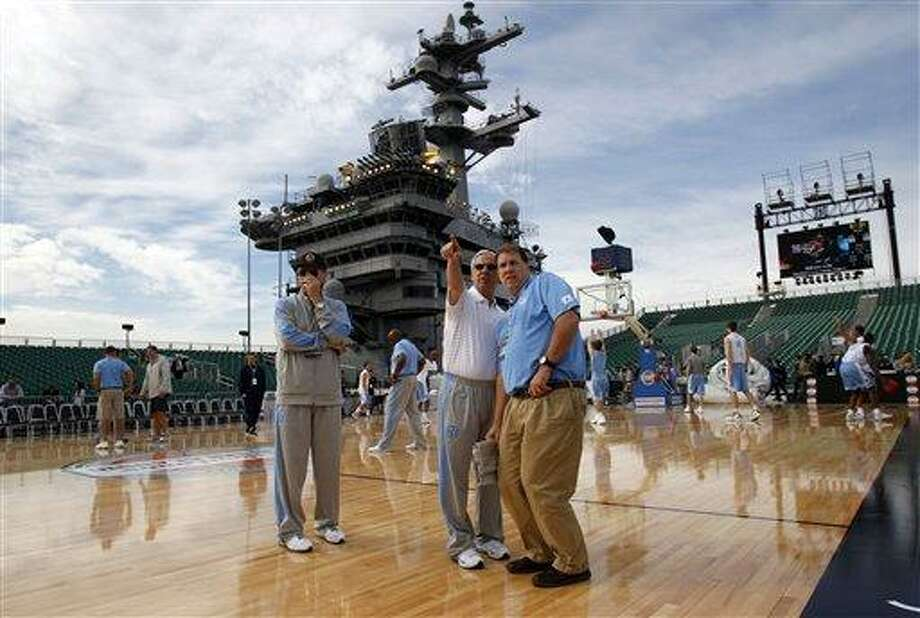 North Carolina coach Roy Williams, center left, points to something on the horizon as he talks with team administrative assistant Steven Kirschner during practice before the Carrier Classic NCAA college basketball game against Michigan State aboard the USS Carl Vinson, Friday, Nov. 11, 2011, in Coronado, Calif. (AP Photo/Lenny Ignelzi) Photo: AP / AP