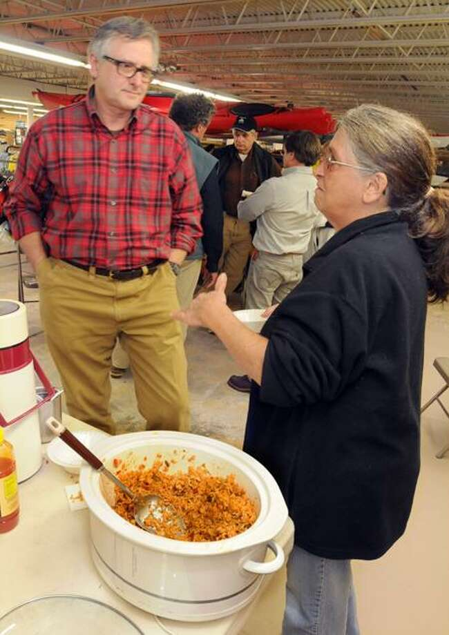 Mara Lavitt/Register photo: Mark Enie of North Cove Outfitters, left, chats with Deb Davis of Norwich after the Squirrel Safari class, while squirrel jambalaya awaits in the slow cooker.
