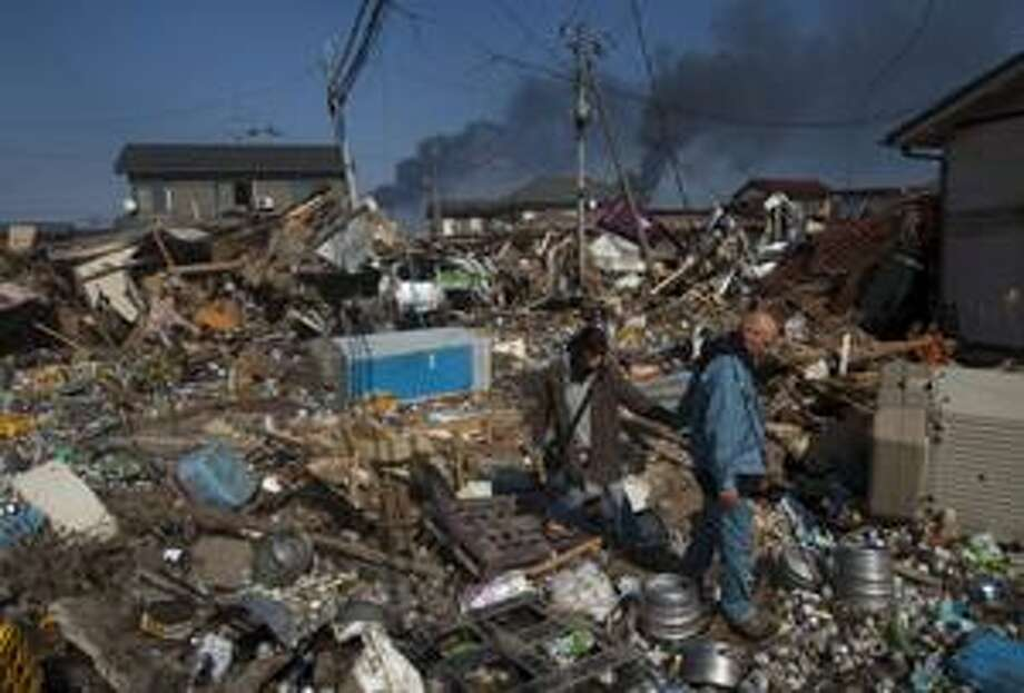 A Japanese couple walk through the ruins of their neighborhood in Sendai, northeastern Japan, Sunday, March 13, 2011, two days after the powerful earthquake and tsunami hit the area. (AP Photo/David Guttenfelder) Photo: AP / AP
