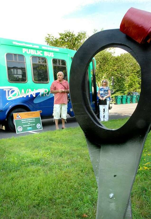 Rich Cabral, Chairman of the Estuary Transit District, left, and vice chairman Leslie Strauss, of the district, speak at the presentation of the first hybrid electric minibuses of their size in New England. The ribbon-cutting took place at Old Lyme Town Hall.    Melanie Stengel/Register