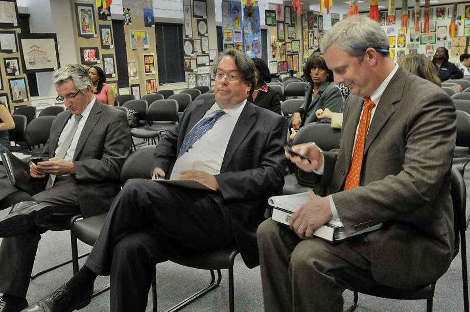 From left, Teachers Union President Dave Cicarella; Renaissance School Services President Richard O'Neill and New Haven public schools COO Will Clark consult their electronic devices at the New Haven Board of Education meeting Monday about the privatization of Roberto Clemente Leadership Academy. Because of a public notice error, the proposal will be discussed at the next board meeting. (Melanie Stengel/Register)