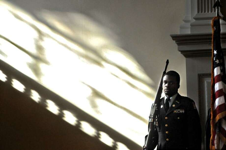 Daishawn Crudup, 18, left, of the Hillhouse H.S. Junior ROTC in the Center Church on the Green Friday 11/11/11  stands next to the American Flag during the Retiring of the Colors at  New Haven's annual Veterans Day ceremony.   Photo by Peter Hvizdak / New Haven Register November 11, 2011       ph22405               Connecticut