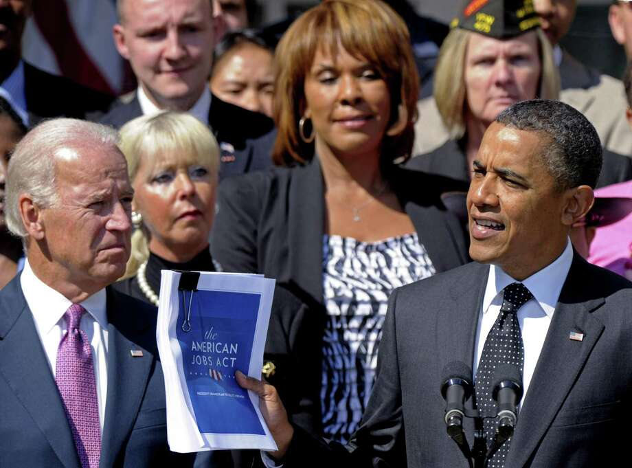 President Barack Obama, accompanied by Vice President Joe Biden and others, holds up a copy of his American Jobs Act during a statement in the Rose Garden of the White House in Washington Monday. (AP Photo/Susan Walsh) Photo: ASSOCIATED PRESS / AP2011
