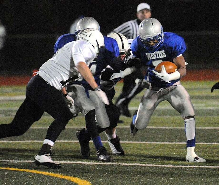 West Haven's Andre Gee looks for room around Xavier's Max Tylki during the first quarter.  Peter Casolino/New Haven Register   11/11/11