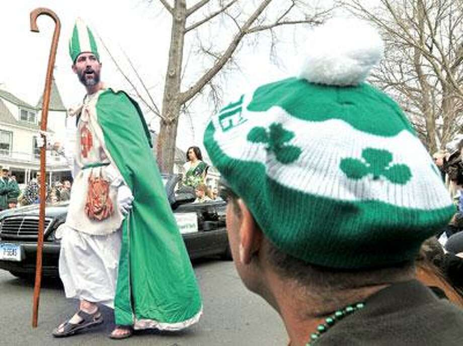 Peter Ortoleva, portraying St. Patrick, walks in Saturday's St. Patrick's Day Parade in Milford. (Brad Horrigan/Register)