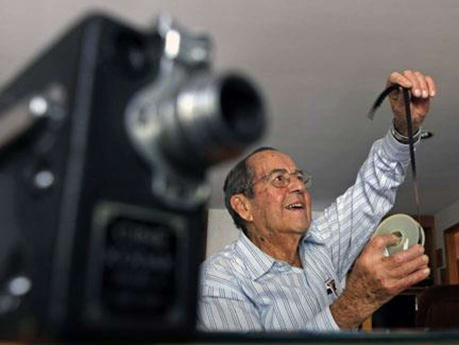 AP Photo by Mike GrollWorld War II veteran Edwin Fitchett looks at film he shot on a Cine Kodak 16mm camera in Japan and the Philippines following the war, in his home in Poughkeepsie, N.Y., on Wednesday, Oct. 5, 2011. Photo: AP / AP
