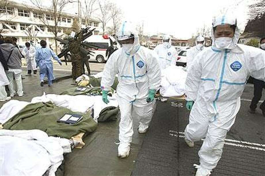 Futaba Kosei Hospital patients who might have been exposed to radiation are carried into the compound of Fukushima Gender Equality Centre in Nihonmatsu in Fukushima Prefecture (state) Sunday morning, March 13, 2011 after being evacuated from the hospital in Futaba town near the troubled Fukushima Dai-ichi nuclear power station. They were waiting for evacuation when an explosion of Unit 1 reactor of the complex blew off the top part of its walls on Saturday, one day after a strong earthquake and tsunami hit northeastern Japan. (AP Photo/The Yomiuri Shimbun, Daisuke Tomita)