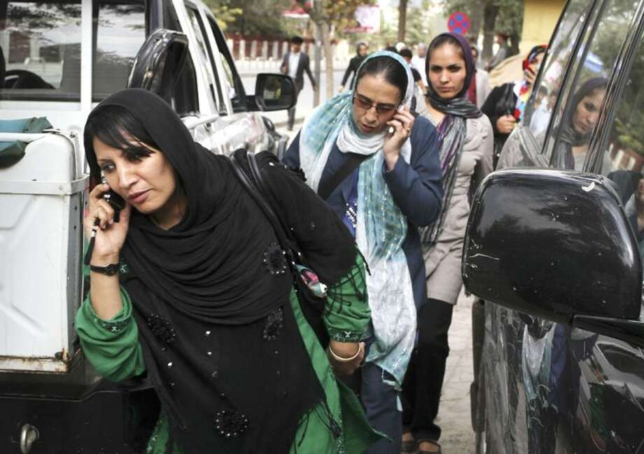Afghan women who work in the health ministry call their families during a battle between the militants and Afghan security forces in Kabul, Afghanistan, Tuesday. Associated Press