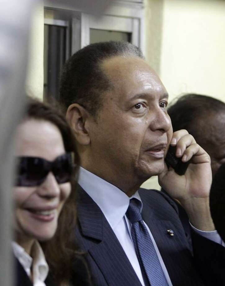 """Former Haitian dictator Jean-Claude """"Baby Doc"""" Duvalier talks by phone next to his wife Veronique Roy upon his arrival to the Toussaint Louverture international airport in Port-au-Prince, Haiti, Sunday Jan. 16, 2011. Duvalier returned Sunday to Haiti after nearly 25 years in exile, a surprising and perplexing move that comes as his country struggles with a political crisis and the stalled effort to recover from last year's devastating earthquake. (AP Photo/Dieu Nalio Chery)"""