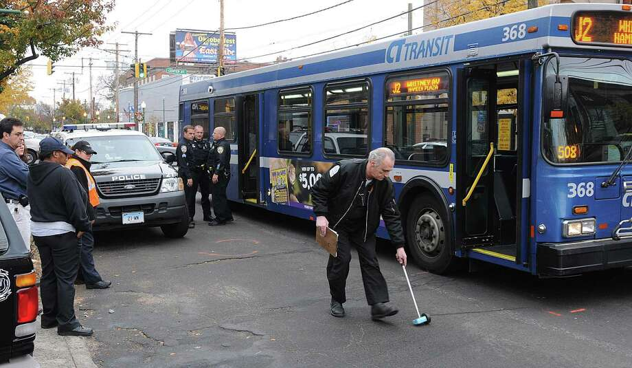 An investigator from CT Transit measures around a CT Transit bus that struck a West Haven police officer Thursday morning on Campbell Avenue. Peter Casolino/Register