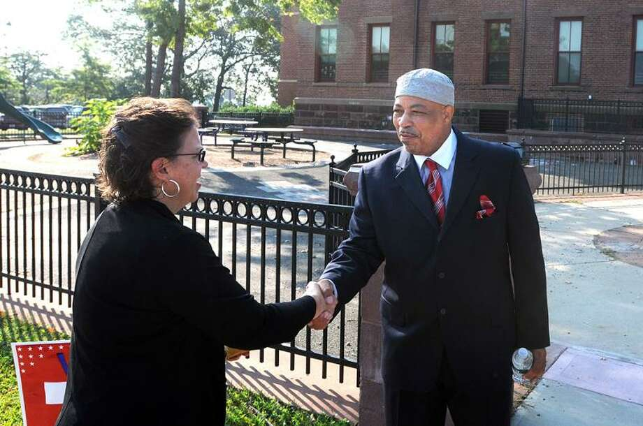 New Haven--Mayoral challenger Clifton Graves greets Jane Savage of New Haven as she arrived at Celentano School to vote in the primary.    Peter Casolino/New Haven Register9/13/11