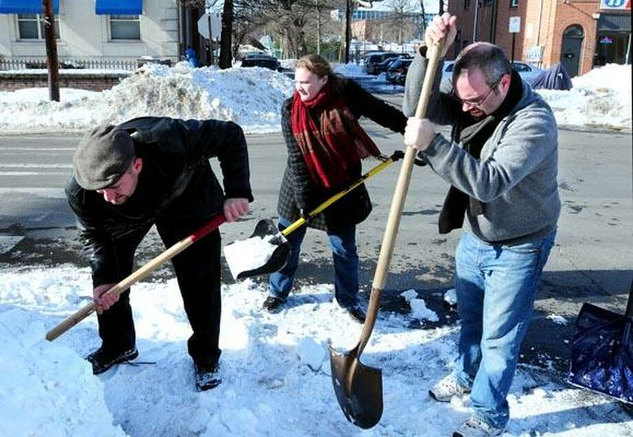 (Left to right) Aaron Goode, Alyson Heimer and Alderman Matt Smith shovel out a storm drain at the corner of Pearl and Orange Sts. in New Haven on 1/17/2011.Photo by Arnold Gold/New Haven Register     AG0399E