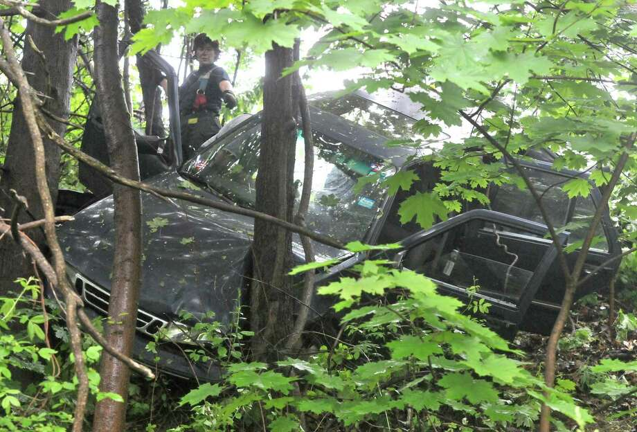 A New Haven Fire Department official examines a car that was driven down an embankment from the Sunset Ridge Apartments' parking lot on Smith Avenue. Brad Horrigan/Register