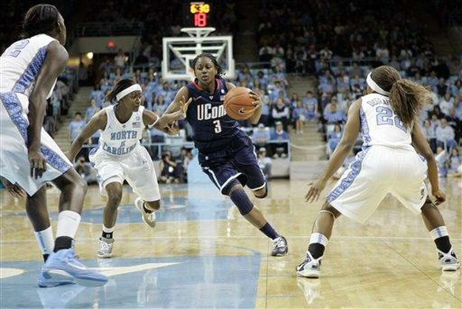 Connecticut guard Tiffany Hayes (3) drives to the basket past North Carolina's She'la White (1),center, Waltiea Rolle (32), left, and Cetera DeGraffenreid (22) during the first half of an NCAA college basketball game in Chapel Hill, N.C., Monday, Jan. 17, 2011. (AP Photo/Jim R. Bounds) Photo: AP / FR3003 AP