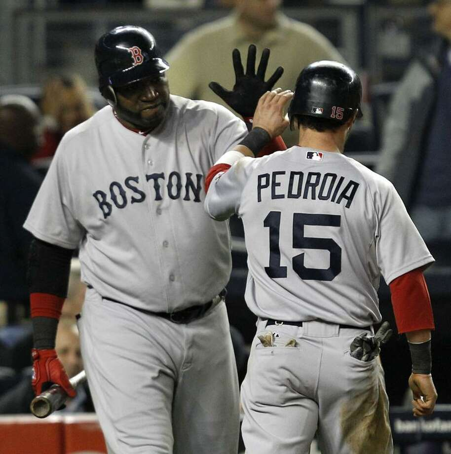 Boston Red Sox David Ortiz greets Dustin Pedroia (15) after Pedroia scored on Alex Rodriguez's seventh-inning error in their baseball game at Yankee Stadium Sunday, May 15, 2011 in New York. (AP Photo/Kathy Willens) Photo: AP / AP2011