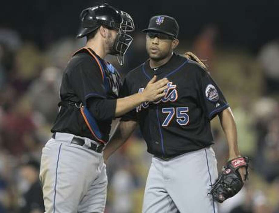 New York Mets catcher A.J. Ellis, left, celebrates beating the Los Angeles Dodgers with relief pitcher Francisco Rodriguez during a baseball game Wednesday, July 6, 2011, in Los Angeles. (AP Photo/Bret Hartman) Photo: AP / FR139655 AP
