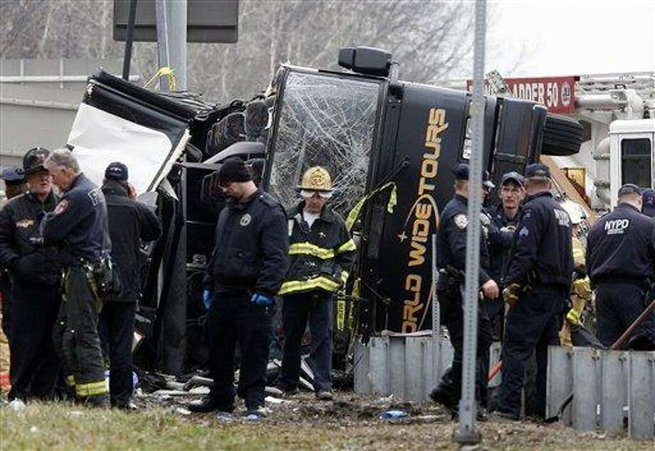 Emergency personnel investigate the scene of a bus crash on Interstate-95 in the Bronx borough of New York Saturday, March 12, 2011. Thirteen people died when the bus, returning to New York from a casino in Connecticut, flipped onto its side and was sliced in half by the support pole for a large sign. (AP Photo/David Karp) Photo: AP / FR50733 AP