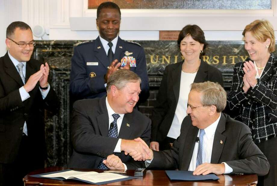 Yale University President Richard Levin, seated right, and U.S. Secretary of the Air Force Michael B. Donley, left, shake hands during a signing ceremony in the Yale Corporation Room establishing an Air Force ROTC program at Yale University. At rear are, from left, Asst. Secretary of the Air Force Daniel B. Ginsberg;  Air Force Gen. Edward A. Rice Jr., Commander, Air Education and Training command; Dorothy K. Robinson, Yale vice president and general counsel; and Linda Koch Lorimer, Yale vice president. Peter Hvizdak/Register