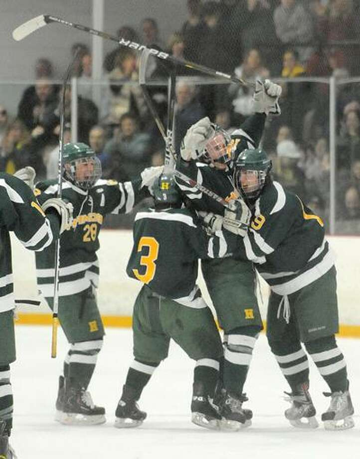 West Haven--Hamden players RJ Ugolik, left, Patrick Lynch, second from left, and Harley Pretty, far right, celebrate with goal scorer James Burt, second from right, during Saturday's Division 1 quarterfinal game at Bennett Rink.  Photo by Brad Horrigan/New Haven Register-03.12.11.