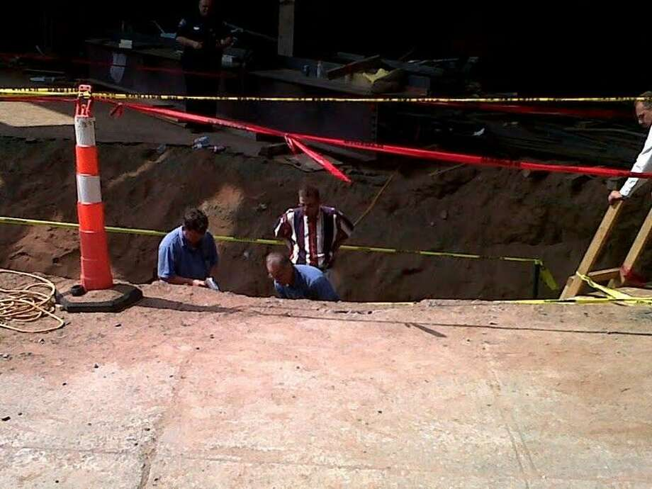 State Archaeologist Nicholas Bellantoni and New Haven police detectives inspect the trench where skeletal remains were found Monday. (William Kaempffer/Register)