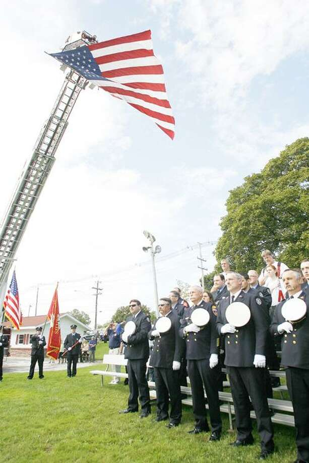 Photo by JOHN HAEGER (Twitter.com/OneidaPhoto) Police and firemen bow their heads during a prayer during the city of Sherrill's 9/11 remembrance on Sunday, Sept. 11, 2011.