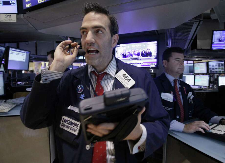 Trader Gregory Rowe, left, works  on the floor of the New York Stock Exchange Wednesday. The Dow Jones industrial average lost 389 points after Italy's borrowing costs soared.(AP Photo/Richard Drew) Photo: ASSOCIATED PRESS / AP2011