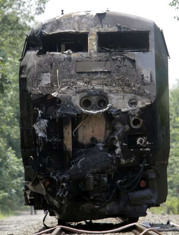 The charred engine of an Amtrak train sits on the track in North Berwick, Maine, after colliding Monday with a tractor-trailer. The truck driver was killed. Associated Press Photo: AP / AP