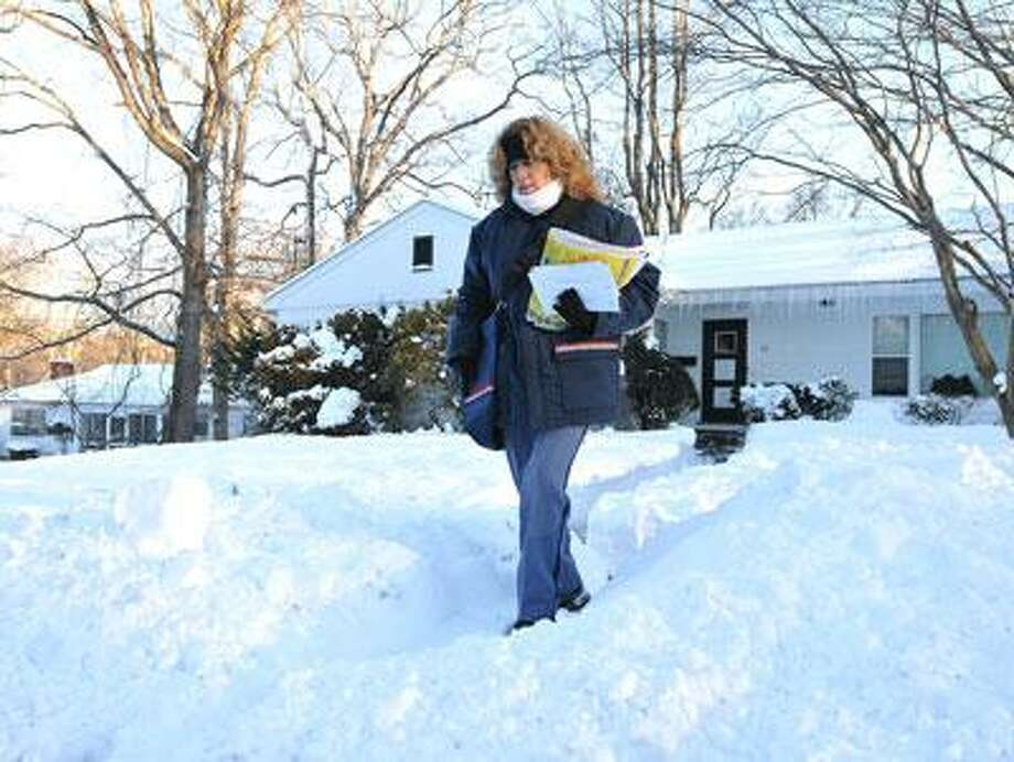 Letter Carrier Martha Phelan makes her way back to the road as she delivered mail along Whittier Road in New Haven. She has been a carrier for 28-years, and this is one of the worst storms she can remember. (Peter Casolino/New Haven Register)
