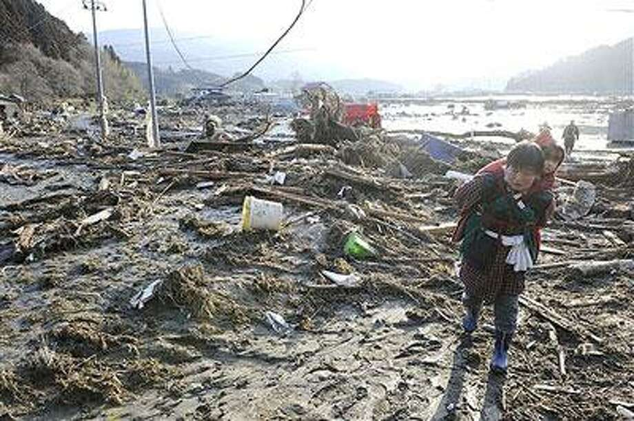 A woman, carrying a child on her back, walks over tsunami-drifted debris and mud in Rikuzentakada, Iwate Prefecture, Saturday morning, March 12, 2011 after Japan's biggest recorded earthquake slammed into its eastern coast Friday. (AP Photo/Kyodo News)