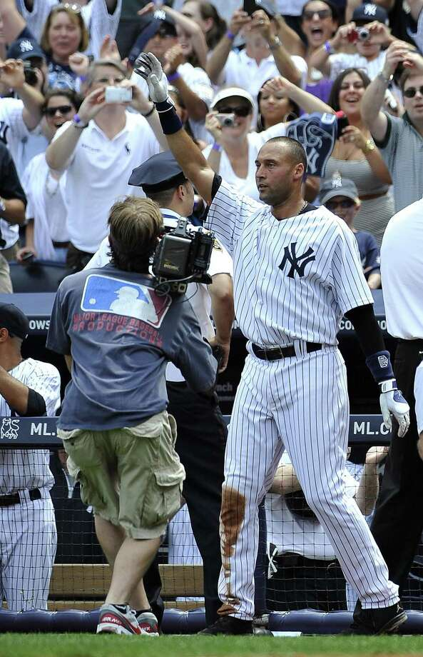 New York Yankees Derek Jeter waves to the cheers of the crowd after he hit a solo home run,  for his 3,000th career hit off of Tampa Bay Rays starting pitcher David Price in the third inning of a baseball game on Saturday, July 9, 2011 at Yankee Stadium in New York. (AP Photo/Kathy Kmonicek) Photo: ASSOCIATED PRESS / AP2011