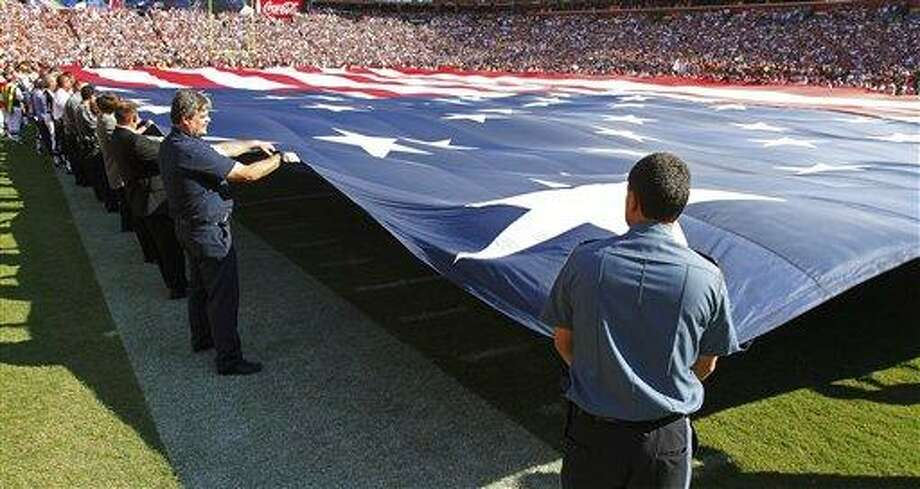 A giant US Flag is waves across the field before an NFL football game between the Washington Redskins and the New York Giants in Landover, Md., on Sunday, Sept. 11, 2011.  (AP Photo/J. David Ake) Photo: AP / AP