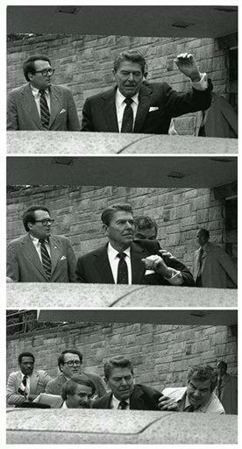 In this March 30, 1981 file photo, President Reagan waves, then looks up before being shoved into Presidential limousine by Secret Service agents after being shot outside a Washington hotel Monday, March 30, 1981. A newly released Secret Service audiotape from the attempted assassination of Ronald Reagan sheds lights on the chaotic aftermath when neither the president nor his agents realized he'd been shot. (AP Photo/Ron Edmonds) Photo: ASSOCIATED PRESS / AP1981