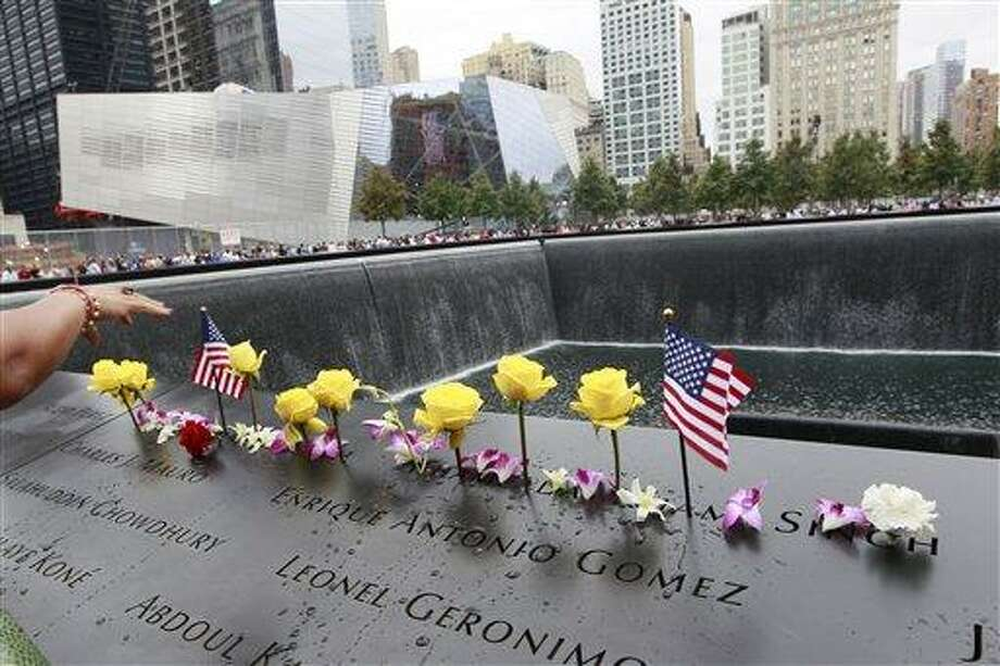 Flowers and American flags are arranged on the north pool of the National September 11 Memorial during a ceremony marking the 10th anniversary of the attacks at the World Trade Center, Sunday, Sept. 11, 2011 in New York.  (AP Photo/Mary Altaffer) Photo: ASSOCIATED PRESS / AP2011