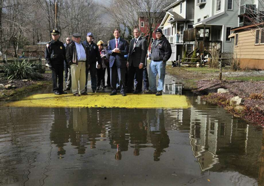 Shelton- U.S. Sen. Richard Blumenthal, center, joins Shelton Mayor Mark Lauretti (next right),  residents, press ,and safety officials as he checks out the flooded Maples area of Shelton on Friday.  Melanie Stengel/Register   3/11/11