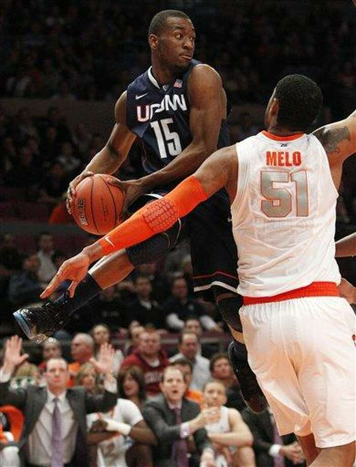 Connecticut's Kemba Walker (15) passes away from Syracuse's Fab Melo (51) during the first half of an NCAA college basketball game at the Big East Championship Friday, March 11, 2011, in New York. (AP Photo/Frank Franklin II) Photo: AP / AP