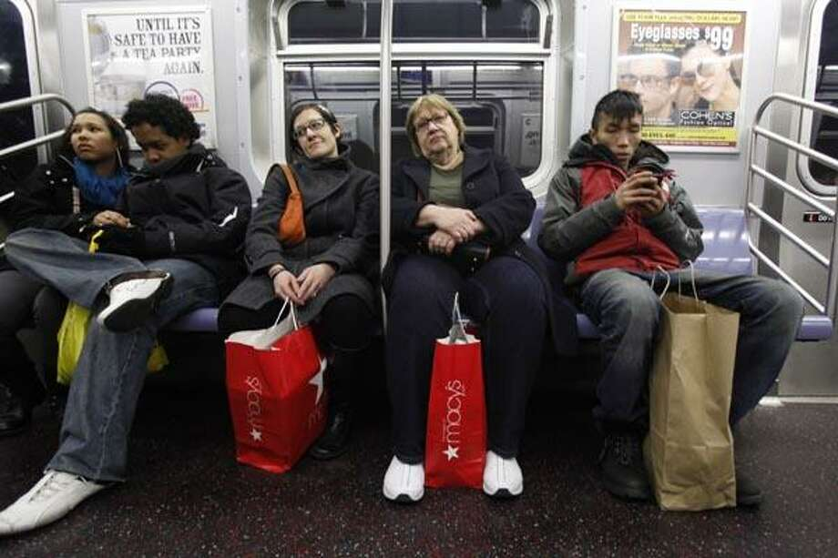 FILE - In this Dec. 18, 2010 file photo, shoppers ride the F-train, in New York. Retail sales rise for the sixth month in December, capping a rebound year following a deep recession.(AP Photo/Mary Altaffer, file) Photo: AP / AP2010