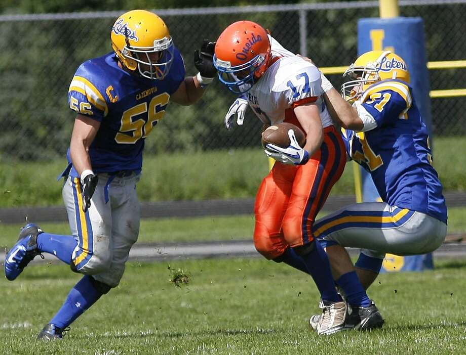 """Dispatch Staff Photo by JOHN HAEGER <a href=""""http://twitter.com/oneidaphoto"""">twitter.com/oneidaphoto</a> Oneida's Tyler Mallinder (19) is tackled for a major loss by Cazenovia's Barclay Talbot (51) and David Ayer (56) on the bobbled snap on 4th down in the first quarter of the game in Cazenovia on Saturday Sept. 10, 2011. Cazenovia won the game 21 to 6."""