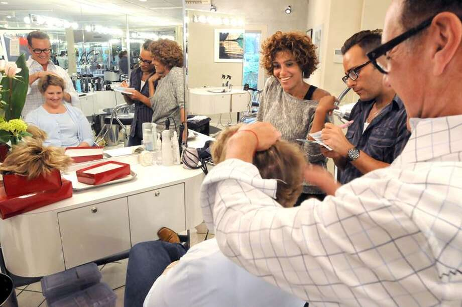Breast cancer survivor Kristen Wall of Guilford has the full attention of stylist Grisel Carrano left, colorist Billy Szostek and Richard Penna, right.