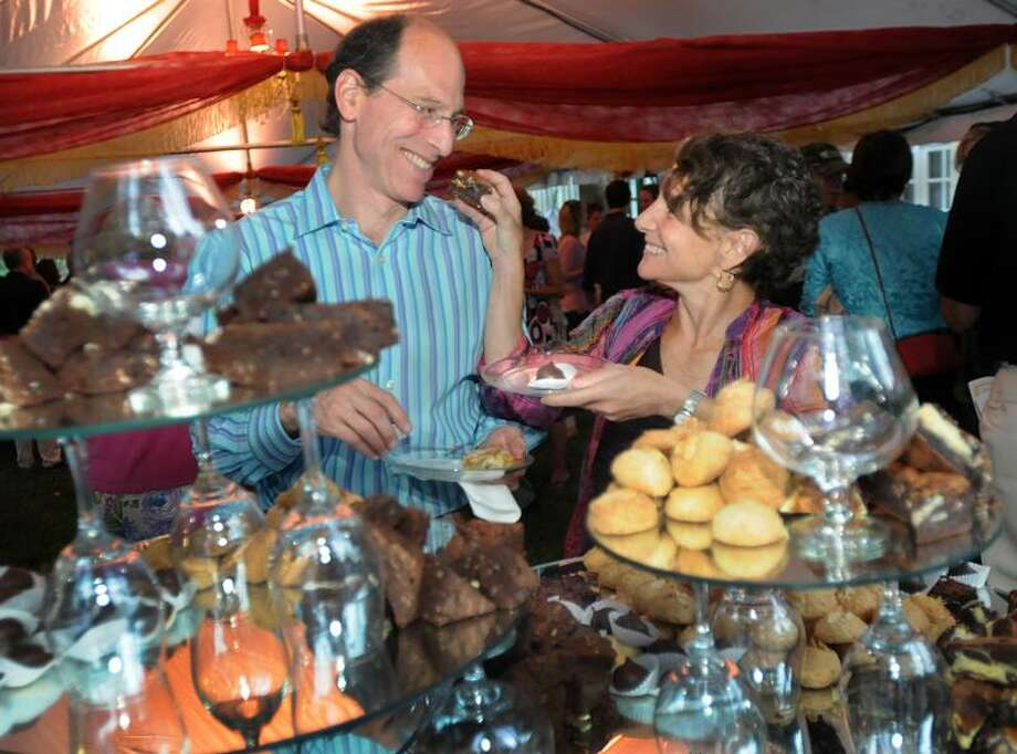 NEW HAVEN_Kal Watsky (L) and Deborah Fried, both of New Haven, share goodies at the dessert table during the Shakespeare in the Park gala at Edgerton Park.   Melanie Stengel/Register